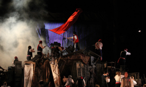 "Students and soldiers build up the wall in the Muny production of ""Les Miserables."""