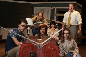 """The cast of """"Night Of The Living Dead"""" huddle around the TV as they sing the compelling """"Broadcast"""" at New Line Theatre. Photo: Jill Ritter Lindberg"""