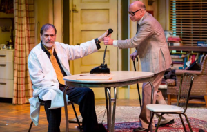 "John Contini as Willie, hands the phone to Al, played by Peter Mayer in the New Jewish Theatre production of ""The Sunshine Boys."""